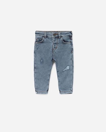 Jeans com pormenor de rasgões