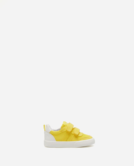 Yellow plimsolls with hook-and-loop straps