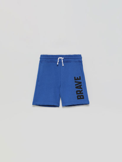 Plush Bermuda shorts with a slogan